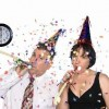Couple celebrates a happy occassion by wearing party hats and blowing horns